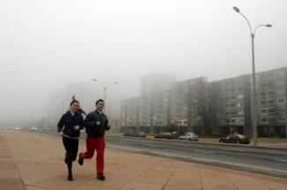 Residents jog by the city's waterfront during a heavy fog day in Montevideo